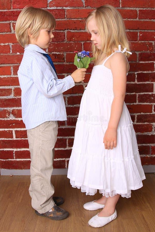 Le garçon donne à une fille des fleurs d'un bouquet photos stock