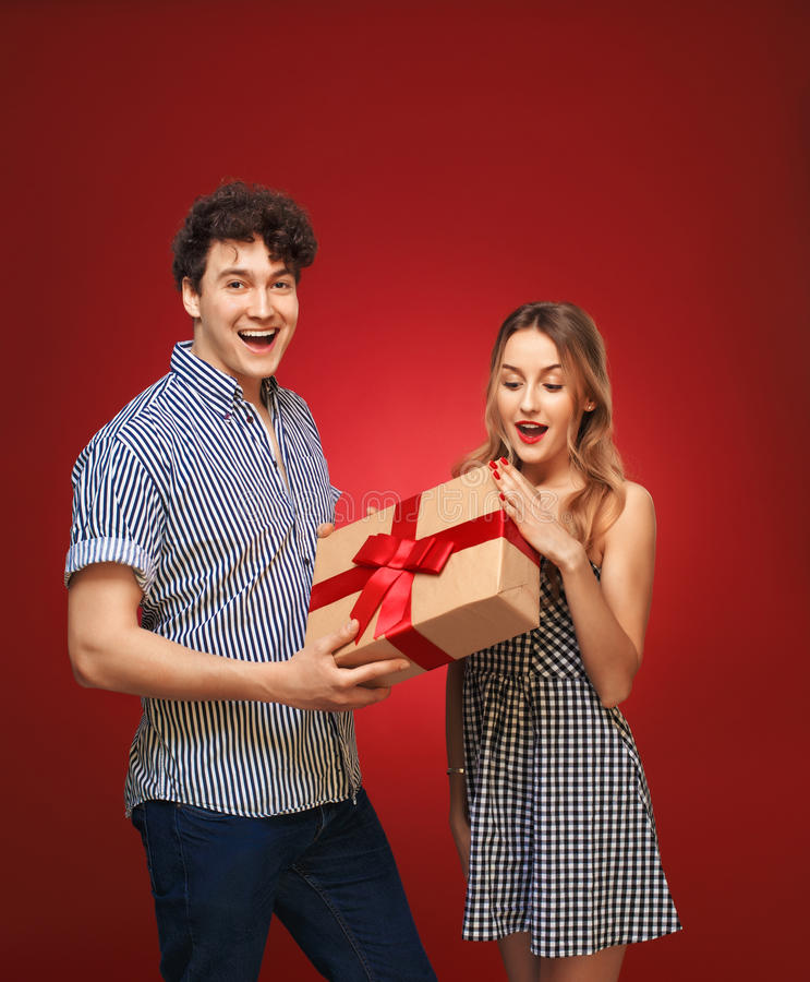 Le garçon donne à une fille un cadeau dans une goupille vers le haut de style, sur un CCB rouge images stock
