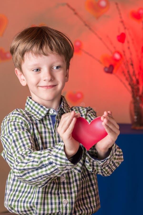 Le garçon donne un coeur rose le jour de valentines photos stock