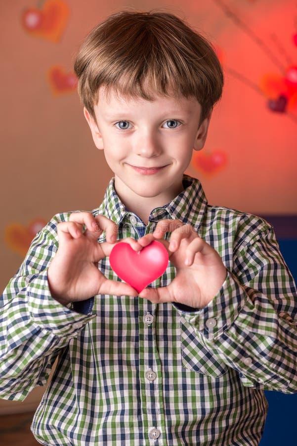 Le garçon donne un coeur rose le jour de valentines images stock