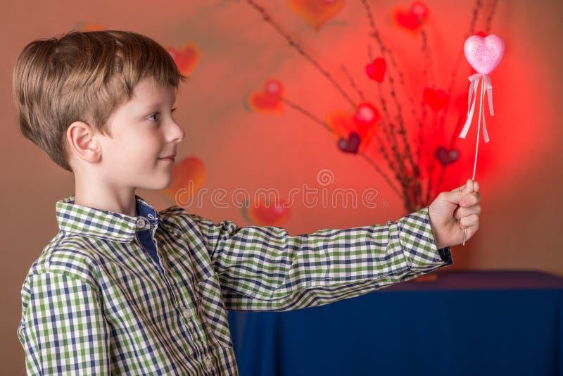 Le garçon donne un coeur rose le jour de valentines photo stock