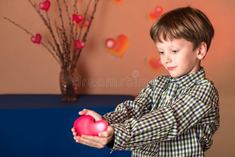 Le garçon donne un coeur rose le jour de valentines photo libre de droits