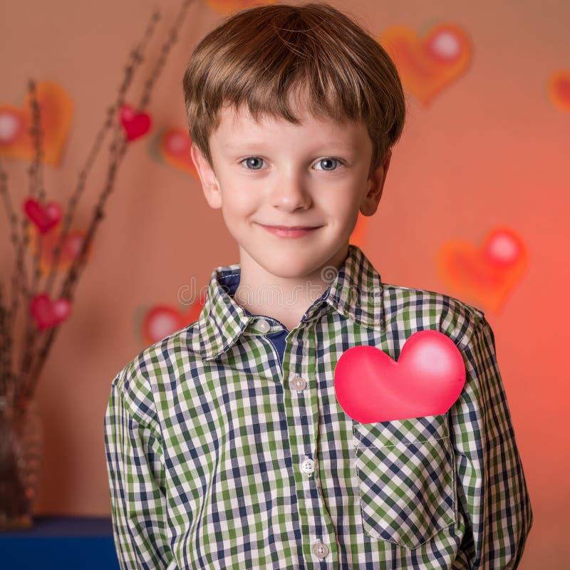 Le garçon donne un coeur rose le jour de valentines images libres de droits