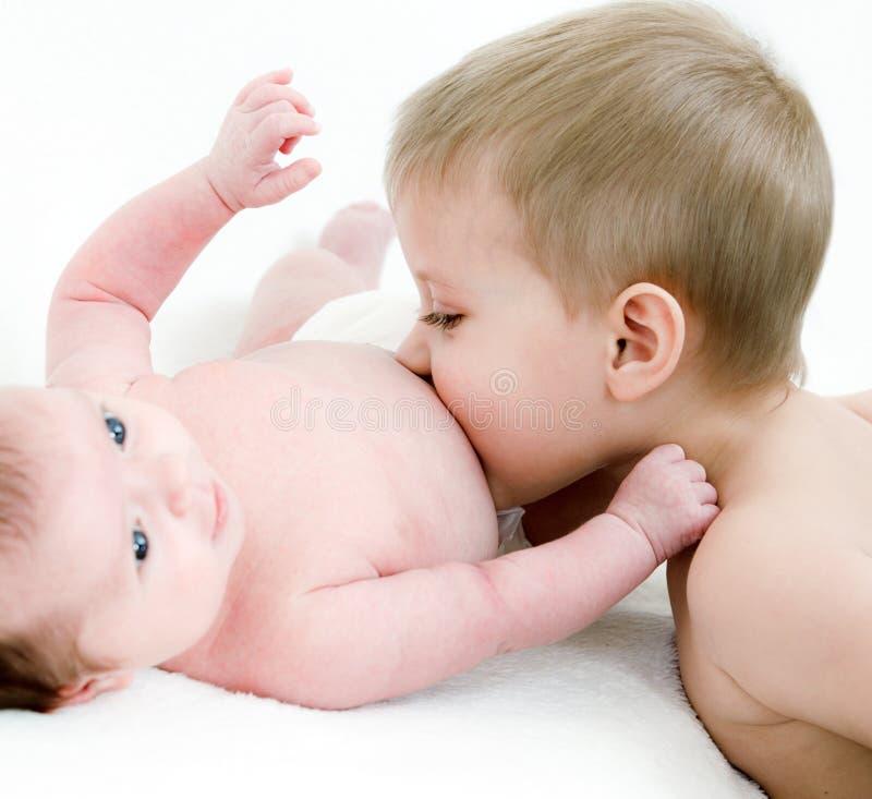 Le garçon embrassent sa soeur nouveau-née images libres de droits