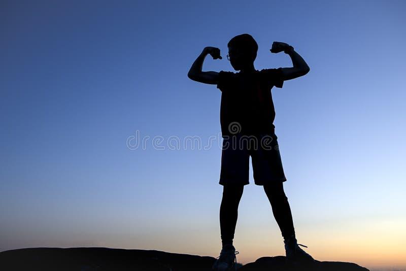 Le garçon en silhouette fait un muscle images stock