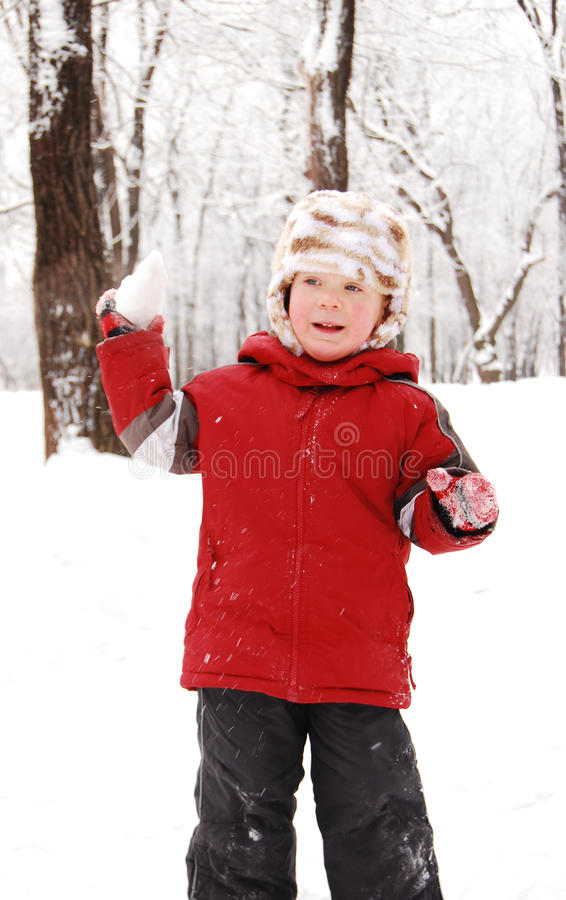 Le garçon en stationnement de l'hiver joue des boules de neige photos stock