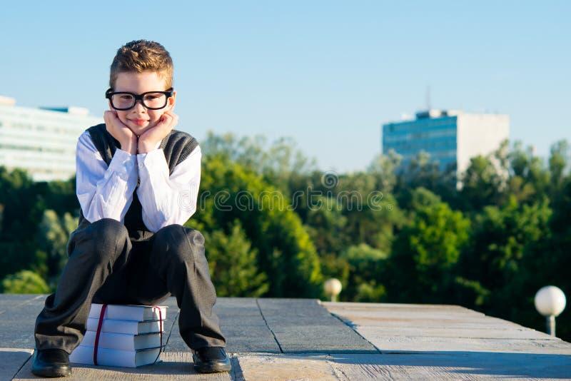 Le garçon en verres, l'écolier s'assied sur des livres, sur la nature en parc photo libre de droits