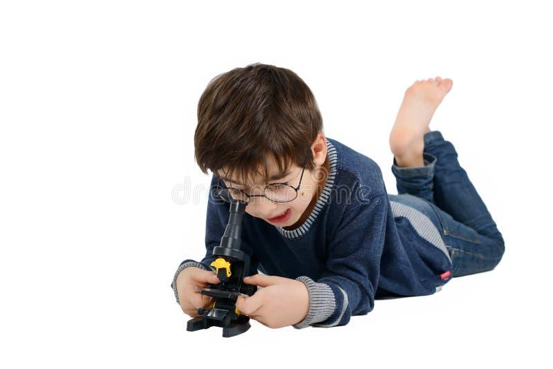 Le garçon en verres regarde dans le microscope images libres de droits