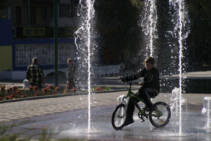 Le garçon essaye de conduire entre la pression d'eau photo libre de droits