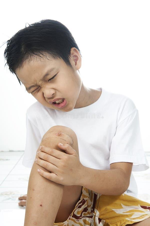 Le garçon est tombé douleur de sa blessure sur le genou image stock