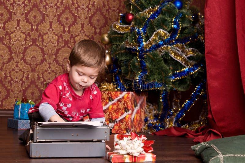 Le garçon estampe la lettre à Santa sur une machine à écrire images stock