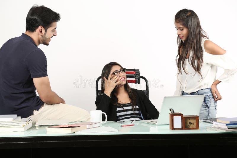 Le garçon et deux filles parle le bavardage avec le visage de sourire image stock