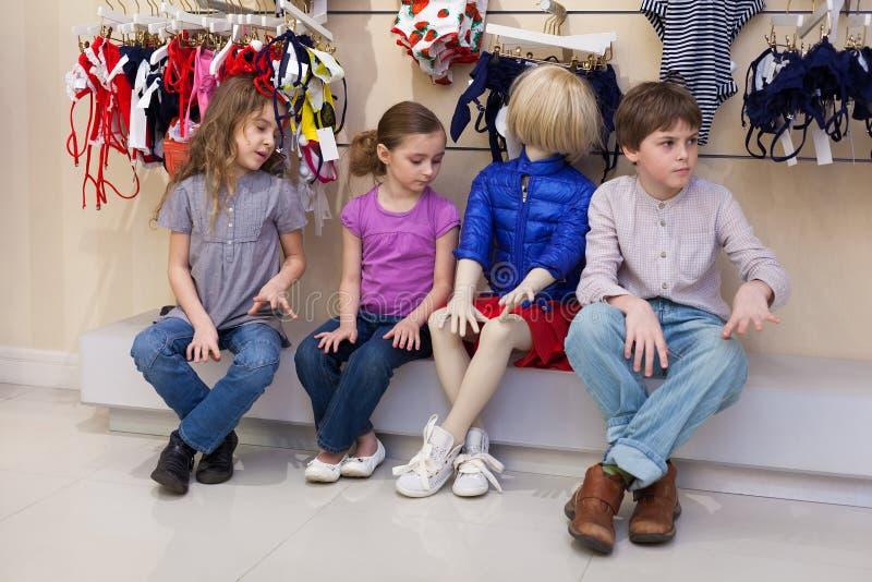 Le garçon et deux filles s'asseyant ainsi que des mannequins images stock