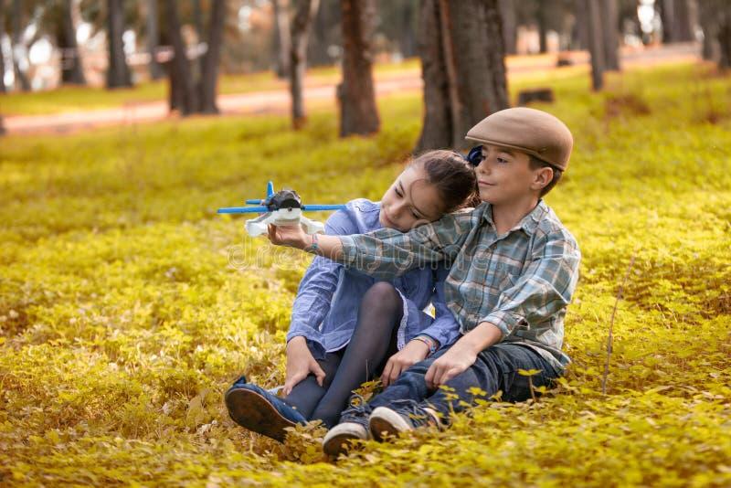 Le garçon et la fille jouant avec un jouet surfacent dans une forêt photos libres de droits