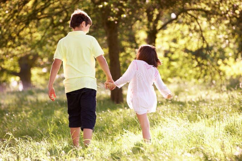 Le garçon et la fille marchant par l'été mettent en place ensemble photo stock