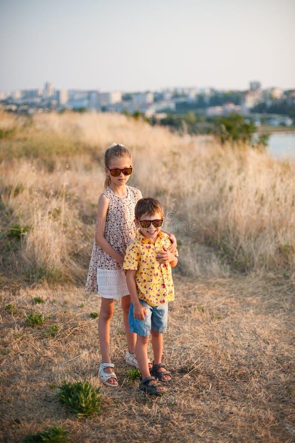 Le garçon et la fille mignons dans des lunettes de soleil se tiennent dans étreindre de champ photo stock