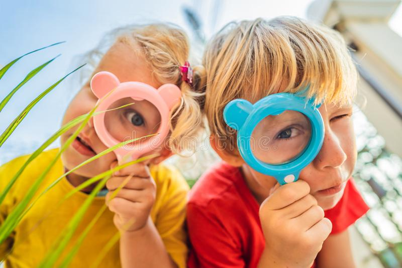 Le garçon et la fille regardent dans une loupe dans la perspective du jardin Enseignement à domicile photo stock