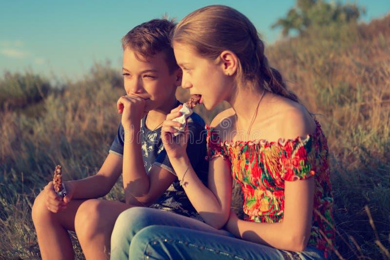 Le garçon et la fille s'asseyent en nature et mangent les barres d'énergie, petit déjeuner pendant une hausse, concept photos stock