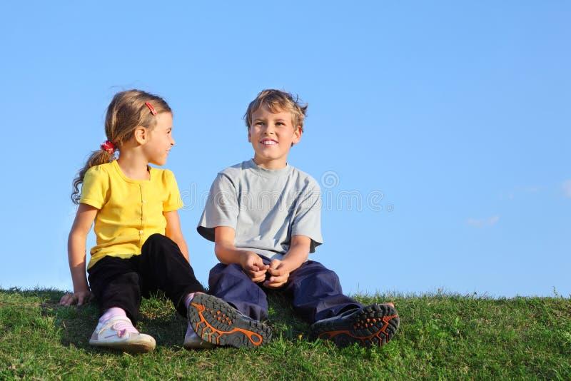 Le garçon et la fille s'asseyent ensemble sur l'herbe photo stock