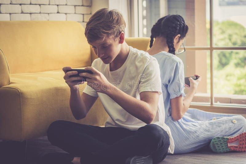 Le garçon et la fille se penchent de retour ensemble et jouant le jeu dans le téléphone portable photographie stock