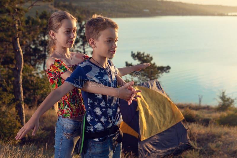 Le garçon et la fille se tiennent sur le fond d'une tente et l'étang, dépeignent l'avion au coucher du soleil, le concept photo stock