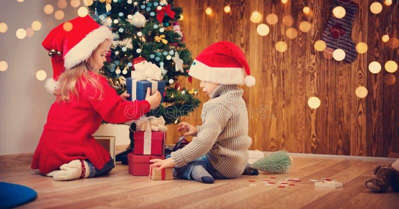 Le garçon et la fille se trouvant sur le plancher avec des présents s'approchent de l'arbre de Noël photos stock
