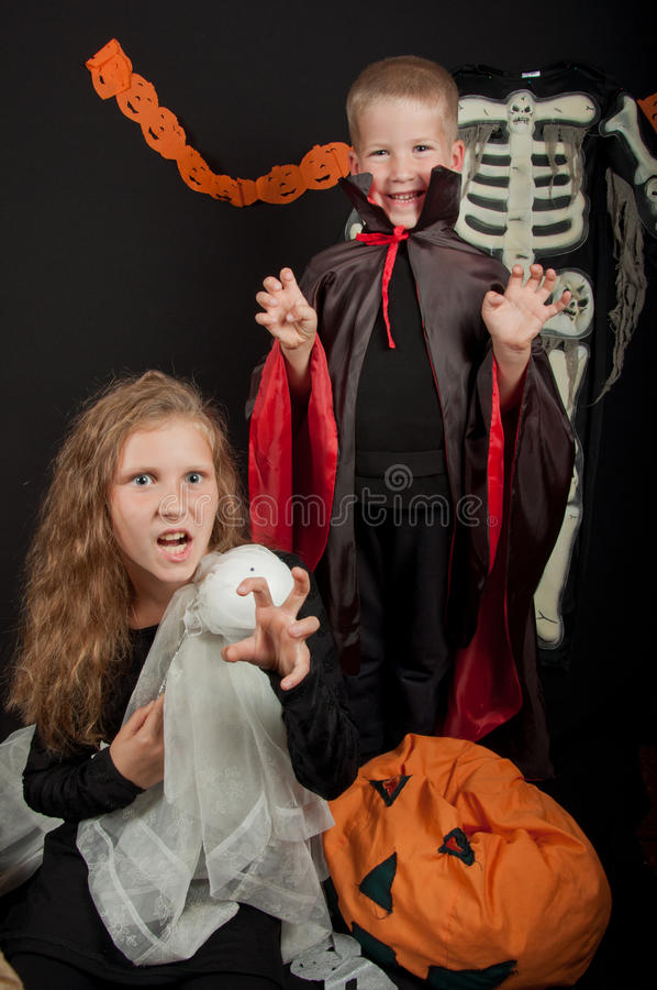 Le garçon et la fille utilisant des costumes de Halloween photographie stock