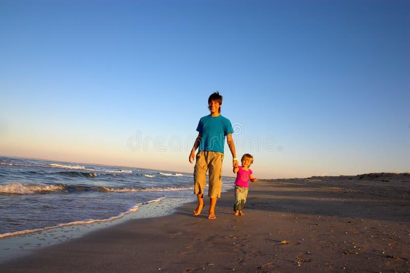 Le garçon et la petite fille marchent le long du littoral photo libre de droits