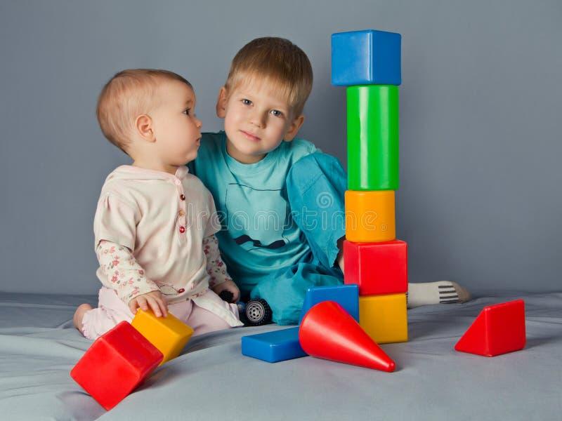 Le garçon et sa petite soeur construisent une tour. photo stock
