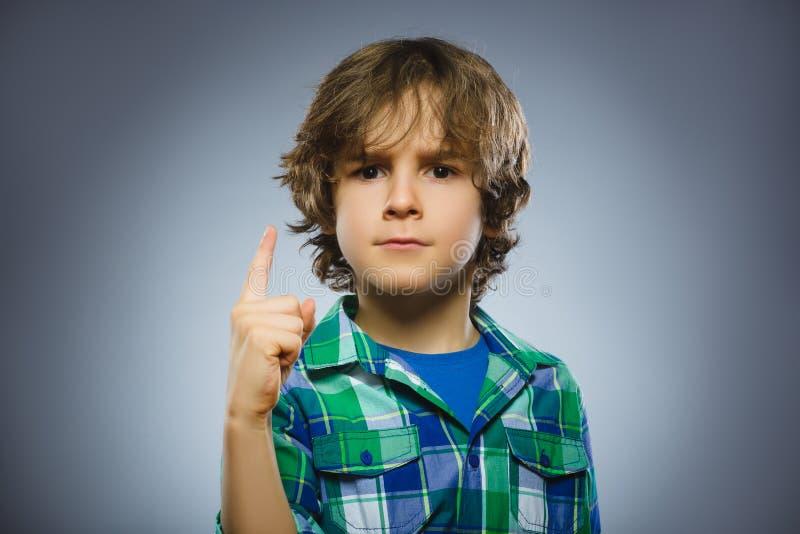 Le garçon fâché contrarié avec menace le doigt d'isolement sur le fond gris photo stock