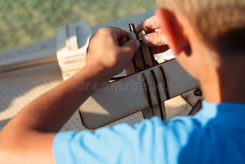 Le garçon faisant l'avion modèle sur la table images libres de droits