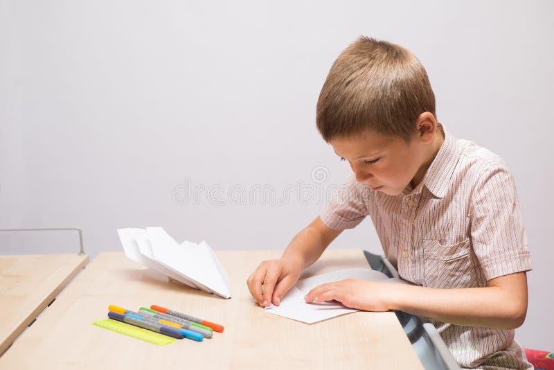 Le garçon faisant les avions de papier photos stock