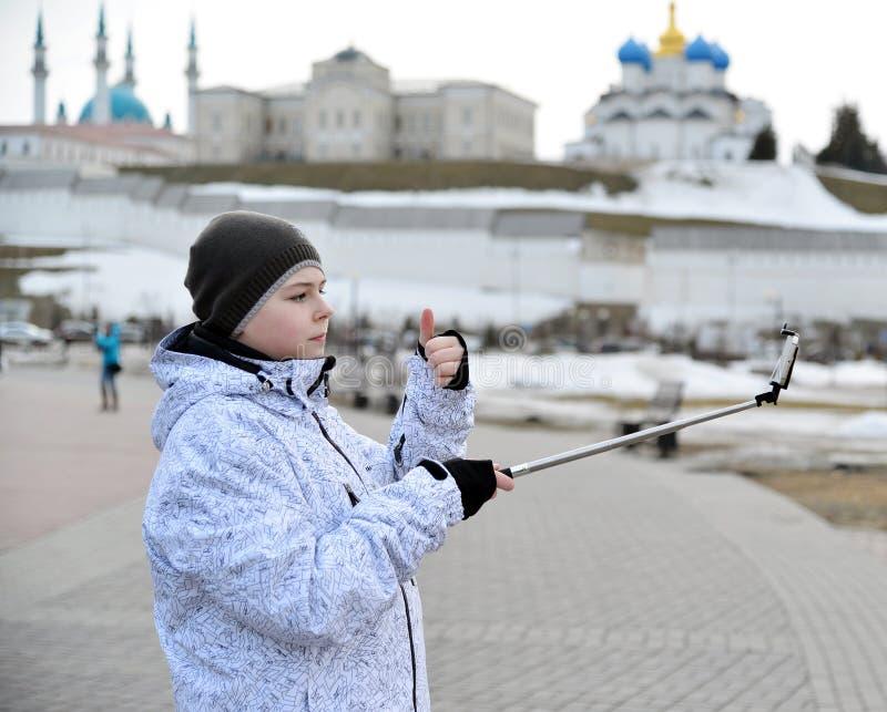 Le garçon fait le selfie au téléphone avec l'auto-bâton contre le contexte de Kazan Kremlin, Russie images libres de droits