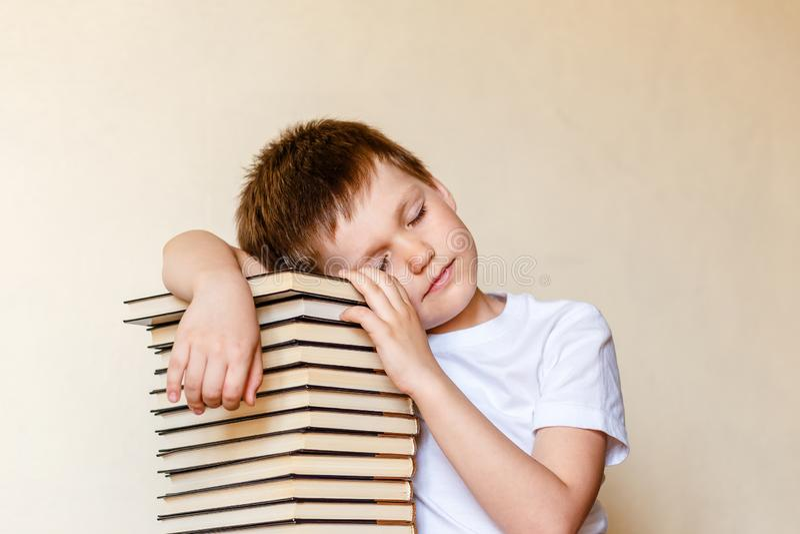 Le garçon fatigué d'esitleti avec des yeux a clôturé le mensonge sur la pile des livres photo stock