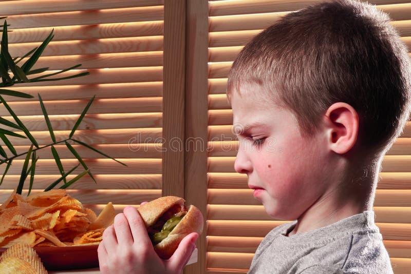 Le garçon fronçant les sourcils regarde le hot dog L'enfant regarde fixement avec dégoût la nourriture insipide dans le café Alim images libres de droits