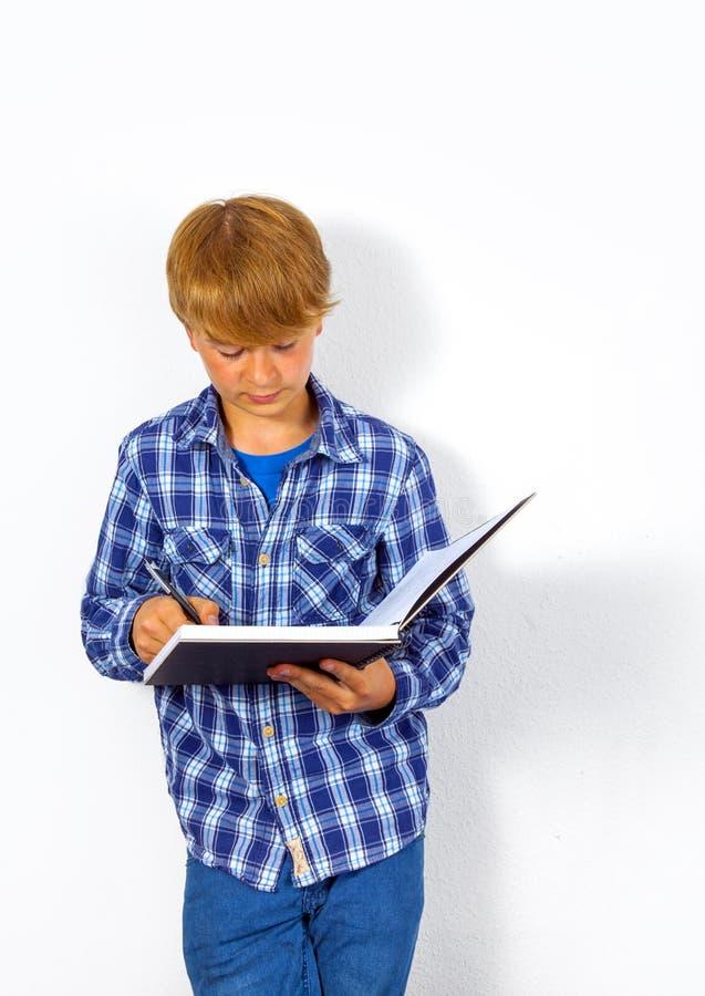 Le garçon futé heureux écrit dans photo stock