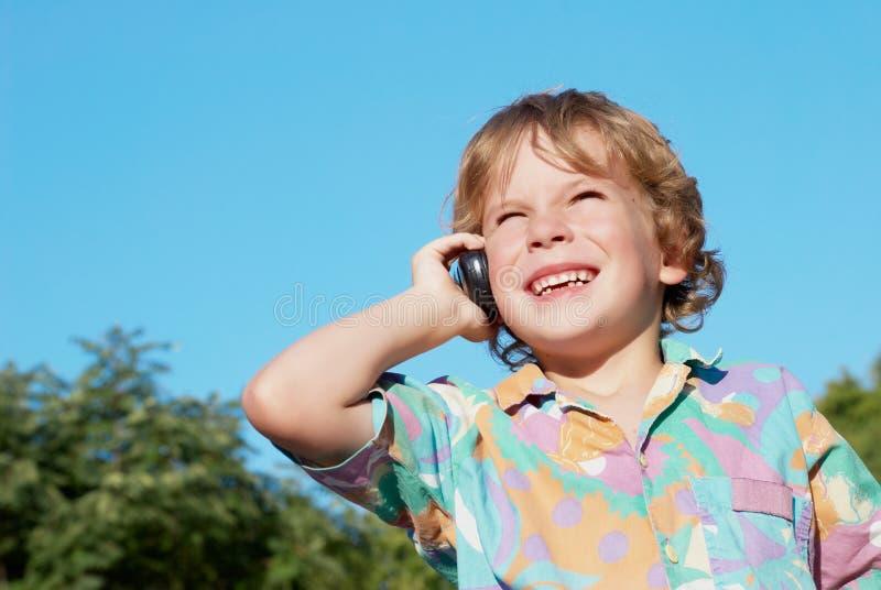 Le garçon gai avec un téléphone portable photographie stock