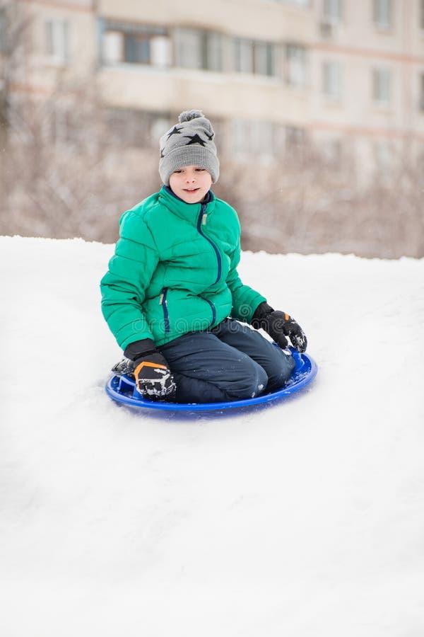 Le garçon glisse vers le bas la colline sur la soucoupe en neige dans la perspective de la multi-maison Concept saisonnier Jour d image stock