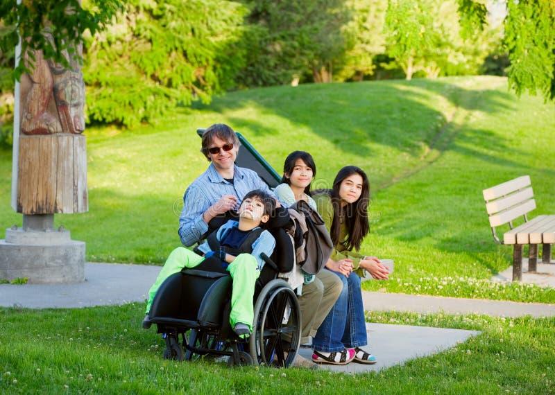 Le garçon handicapé dans le fauteuil roulant avec la famille dehors le jour ensoleillé s'asseyent photo stock