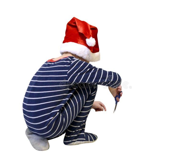 Le garçon heureux avec des ciseaux ouvrent le cadeau d'isolement sur le templa vide blanc image stock