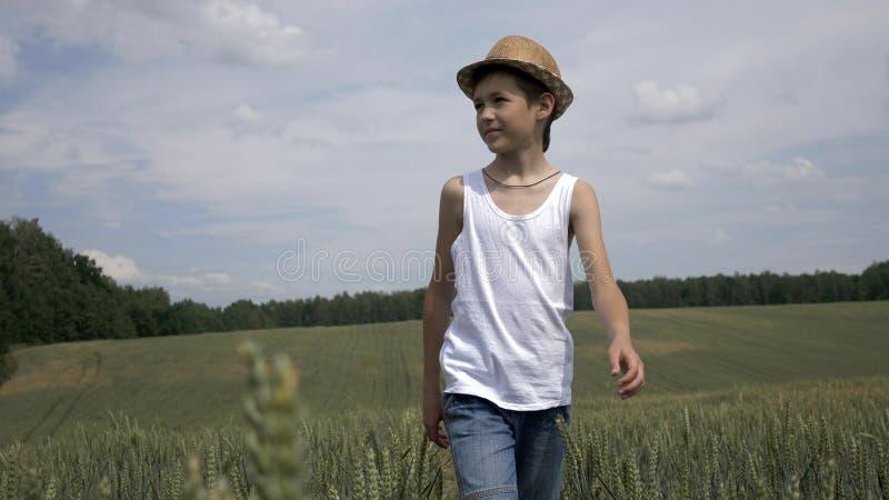 Le garçon heureux d'agriculteur dans un chapeau marche à travers le champ, dehors photos libres de droits
