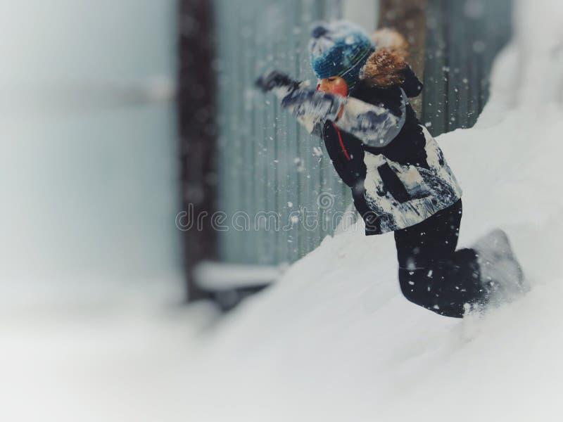 Le garçon heureux en hiver vêtx sauter de la neige et l'endroit pour votre texte photos stock