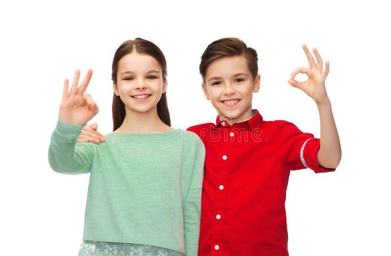Le garçon heureux et la fille montrant la main correcte signent photo libre de droits