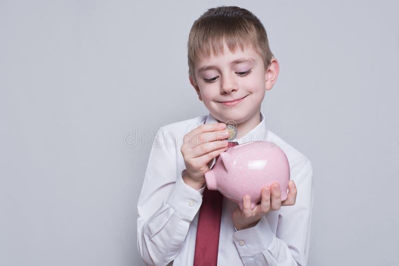 Le gar?on heureux met une pi?ce de monnaie ? une tirelire rose Concept d'affaires Fond clair images stock