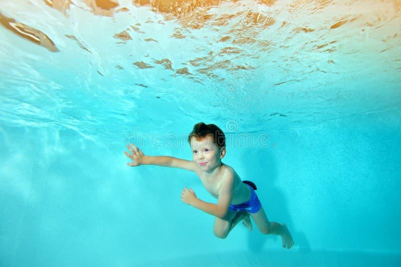 Le garçon heureux nage sous l'eau dans la piscine contre le contexte des lumières lumineuses, semblant parti et du sourire image stock