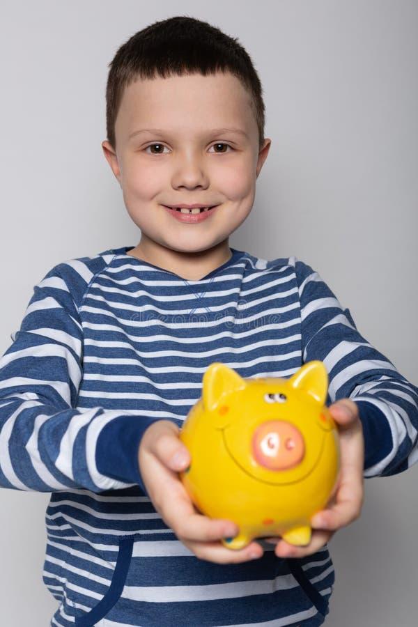 Le garçon heureux sourit et donne ses mains avec un concept de tirelire, de finances et d'épargne photographie stock