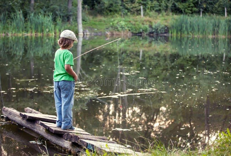Le garçon heureux vont pêcher sur la rivière, un pêcheur d'enfants avec a image libre de droits