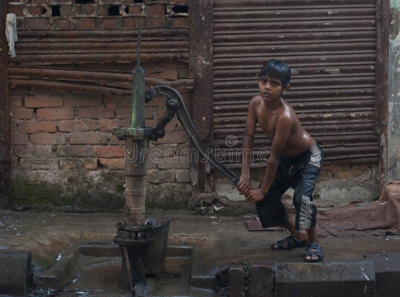 Le garçon indien de Topeless pompe l'eau d'une pompe à eau de rue dans Kolkata, Inde image stock