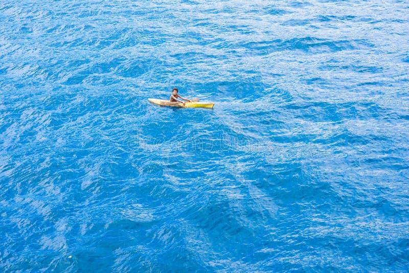 Le garçon indigène barbotant un canoë fait à partir de l'creusé ouvrent une session la mer large près de Solomon Islands photos stock