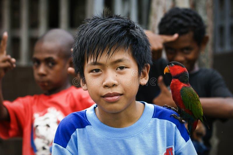 Le garçon indonésien avec un perroquet. photographie stock libre de droits
